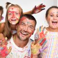 Portrait of a cute happy father with children painting and havinп fun. They are showing their hands painted in bright colors