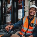 Happy forklift driver sitting in vehicle in warehouse